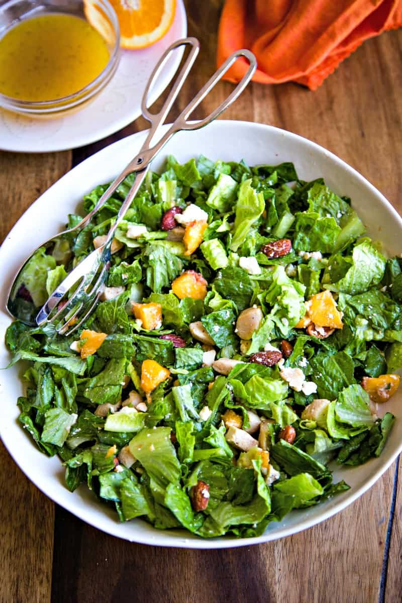 white serving bowl of romaine lettuce, chicken, peaches with salad tongs on a wooden surface