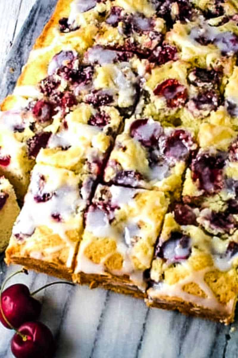 cherry cake cut into squares on a marble board