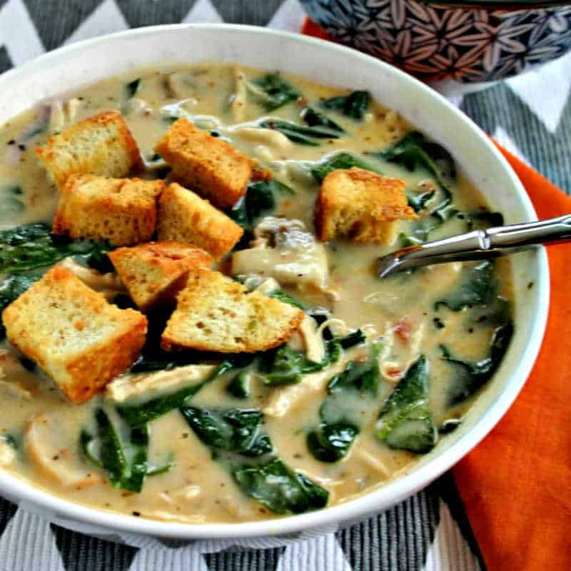 a bowl of chicken florentine soup with toasted croutons