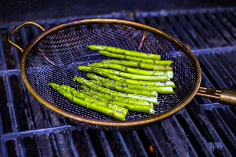 asparagus spears in a grill basket on a gas grill