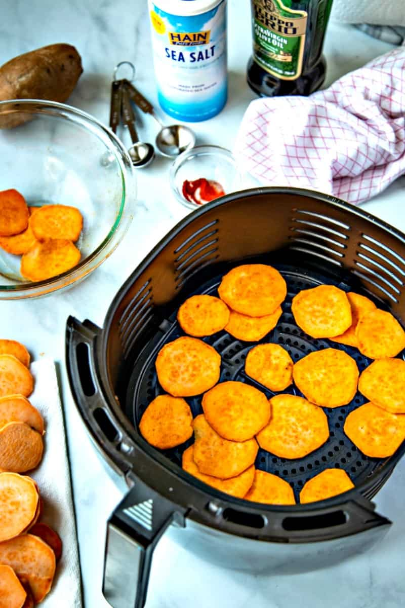 raw sweet potato sliced in air fryer basket