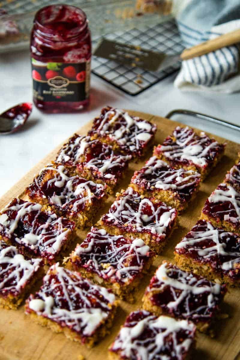 raspberry oatmeal bars on a wooden cutting board with raspberry jam