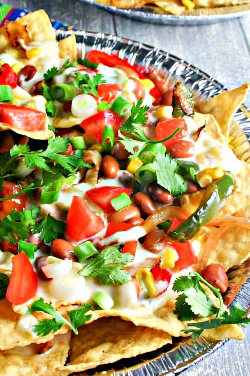 nachos with pinto beans, red bell peppers, and cheese sauce