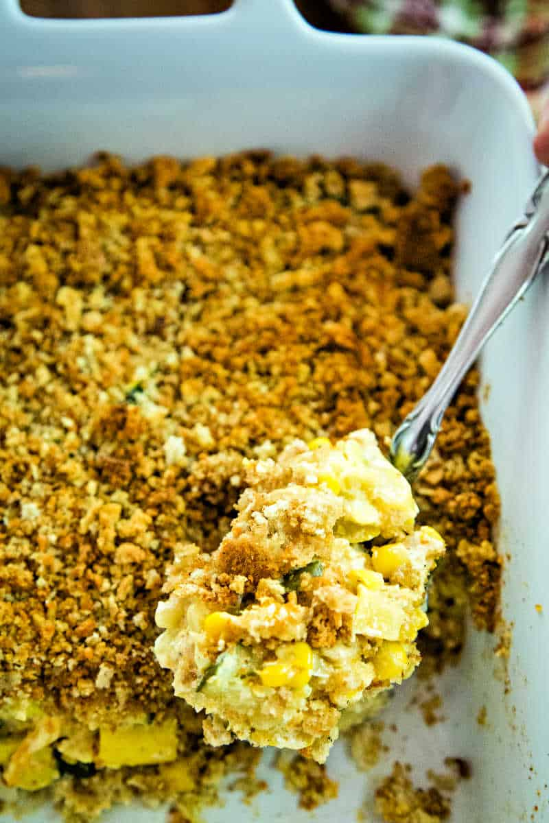 a spoon serving squash and zucchini casserole from a white baking dish