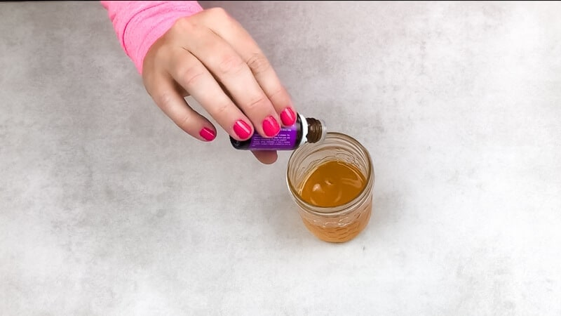 Adding drops of lavender essential oil to shea butter baby balm recipe