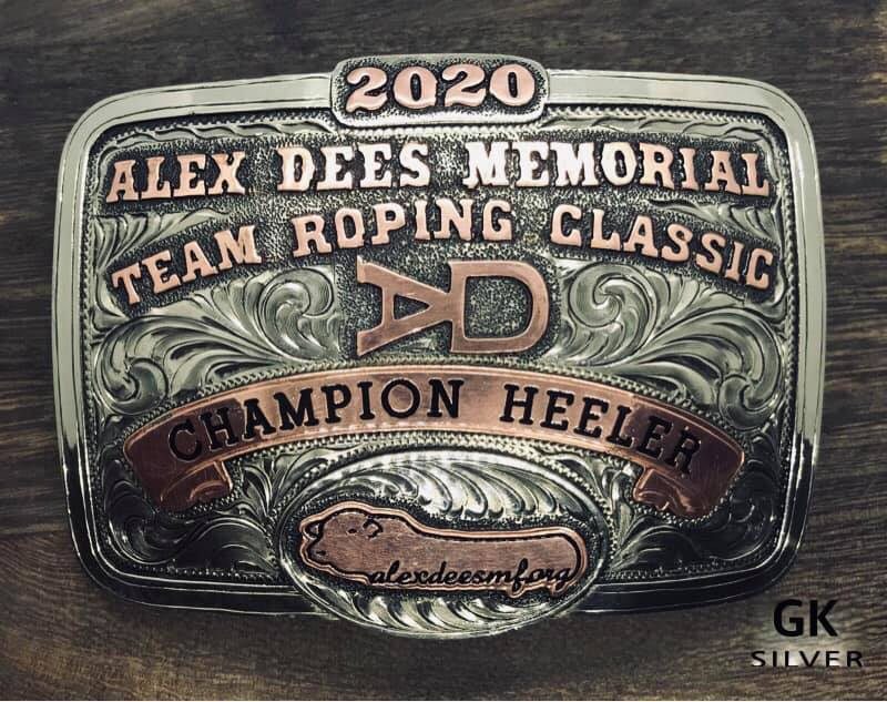 """Close up image of handmade belt buckle which reads: """"Alex Dees Memorial Team Roping Classic Champion Heeler"""""""
