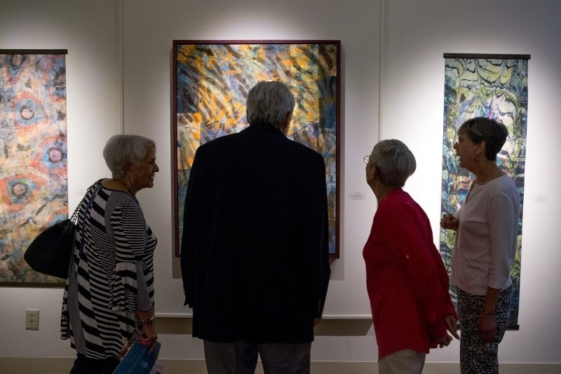 Patrons and a docent look at a painting in the Brenau Presidents Gallery.