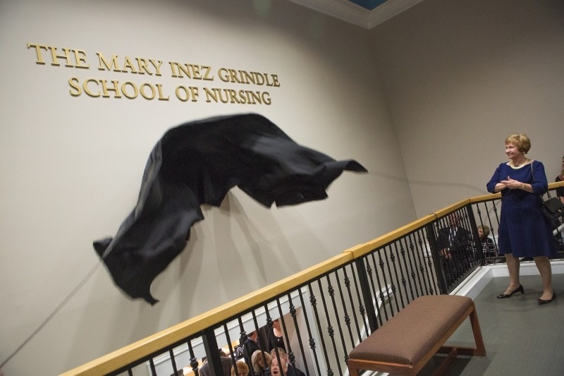 Kay Ivester removes the covering from the sign for the Mary Inez Grindle School of Nursing during the dedication of the Mary Inez Grindle School of Nursing. (AJ Reynolds/Brenau University)