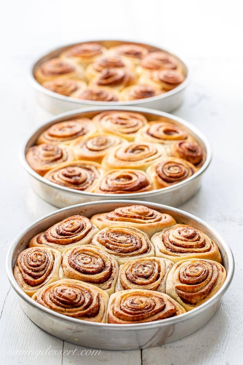 Three pans of baking cinnamon rolls, no frosting