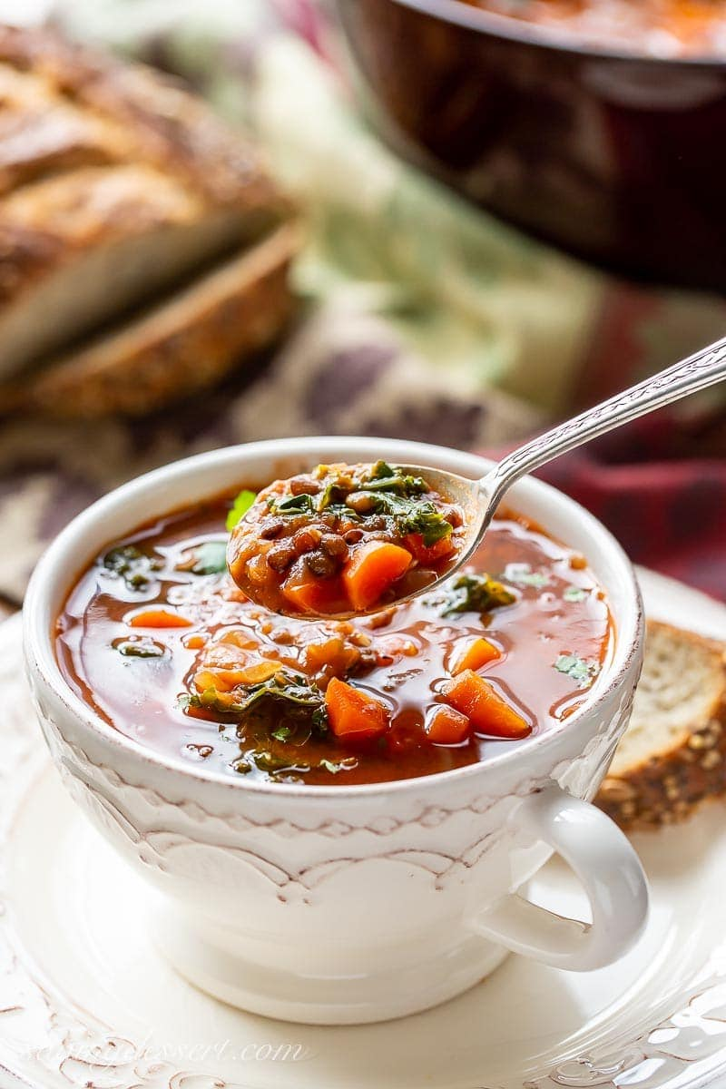 A spoonful of lentil soup with carrots and kale