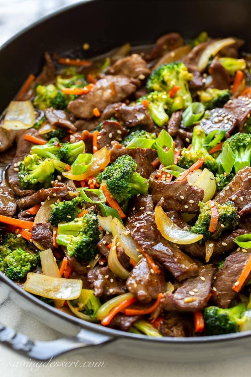 A skillet filled with thin sliced beef, broccoli, carrots and onions topped with sesame seeds