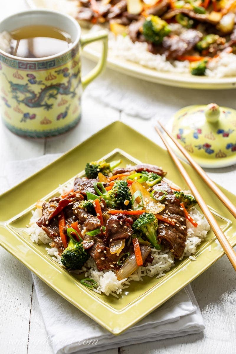 A plate with beef and broccoli stir-fry served over rice with a cup of tea