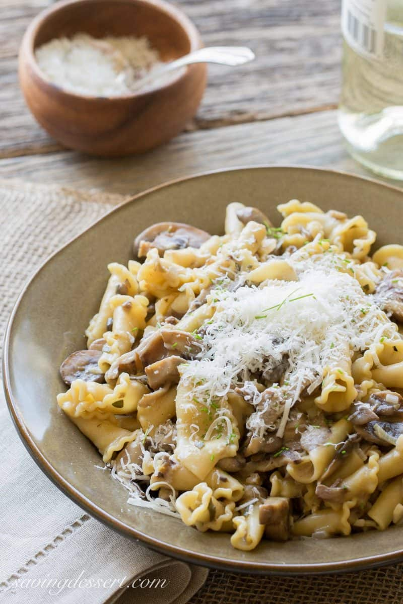 A bowl of Campanella pasta with mushroom sauce topped with Parmesan
