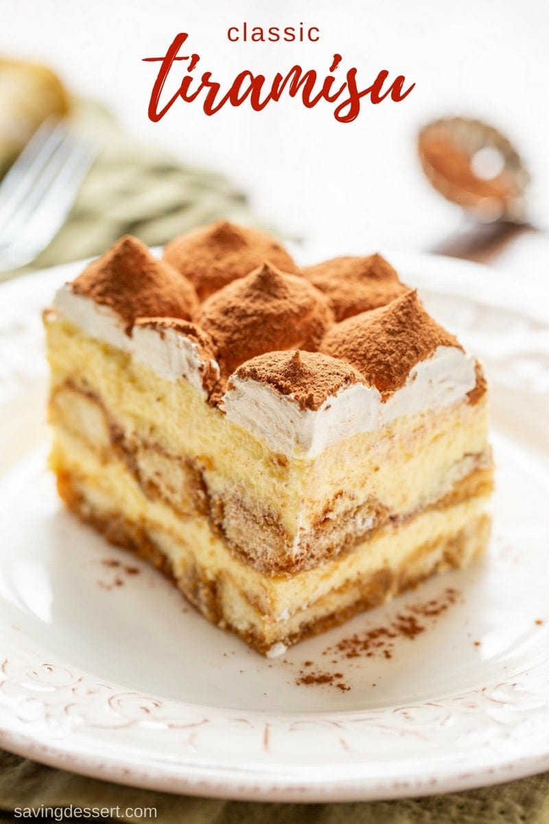 A slice of classic Tiramisu topped with mounds of whipped cream and cocoa powder