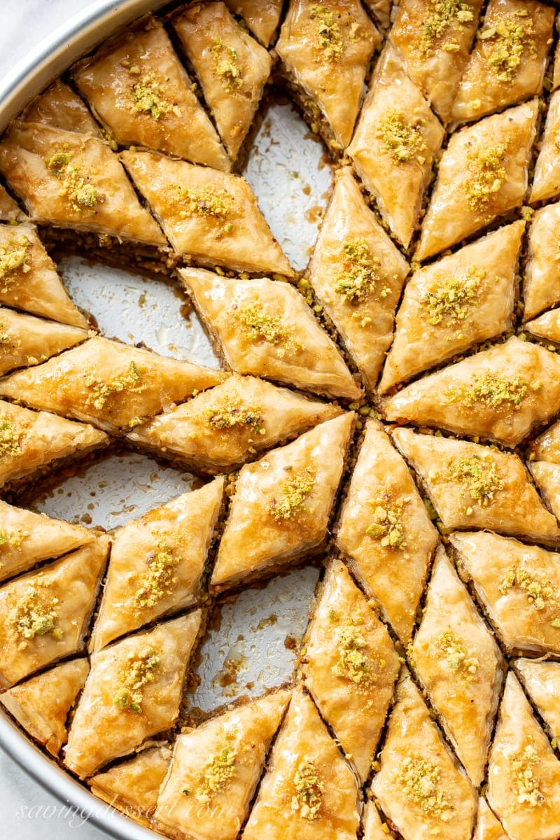 A pan of sliced honey baklava sprinkled with chopped pistachios