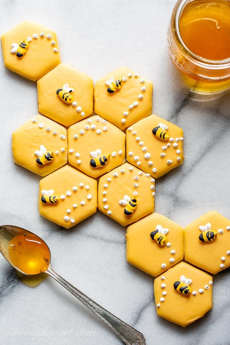 A sugar cookie recipe cut out into a hexagonal shape decorated with honey bees