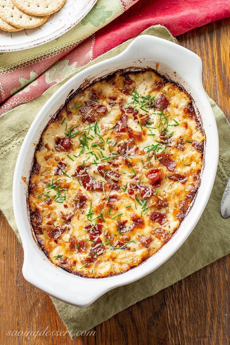 A small casserole dish with caramelized onion dip topped with bacon and chives