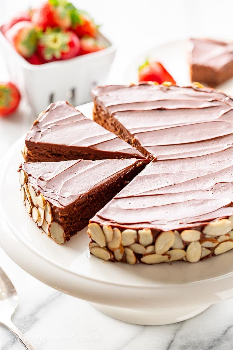 A sliced single layer chocolate almond cake served with strawberries