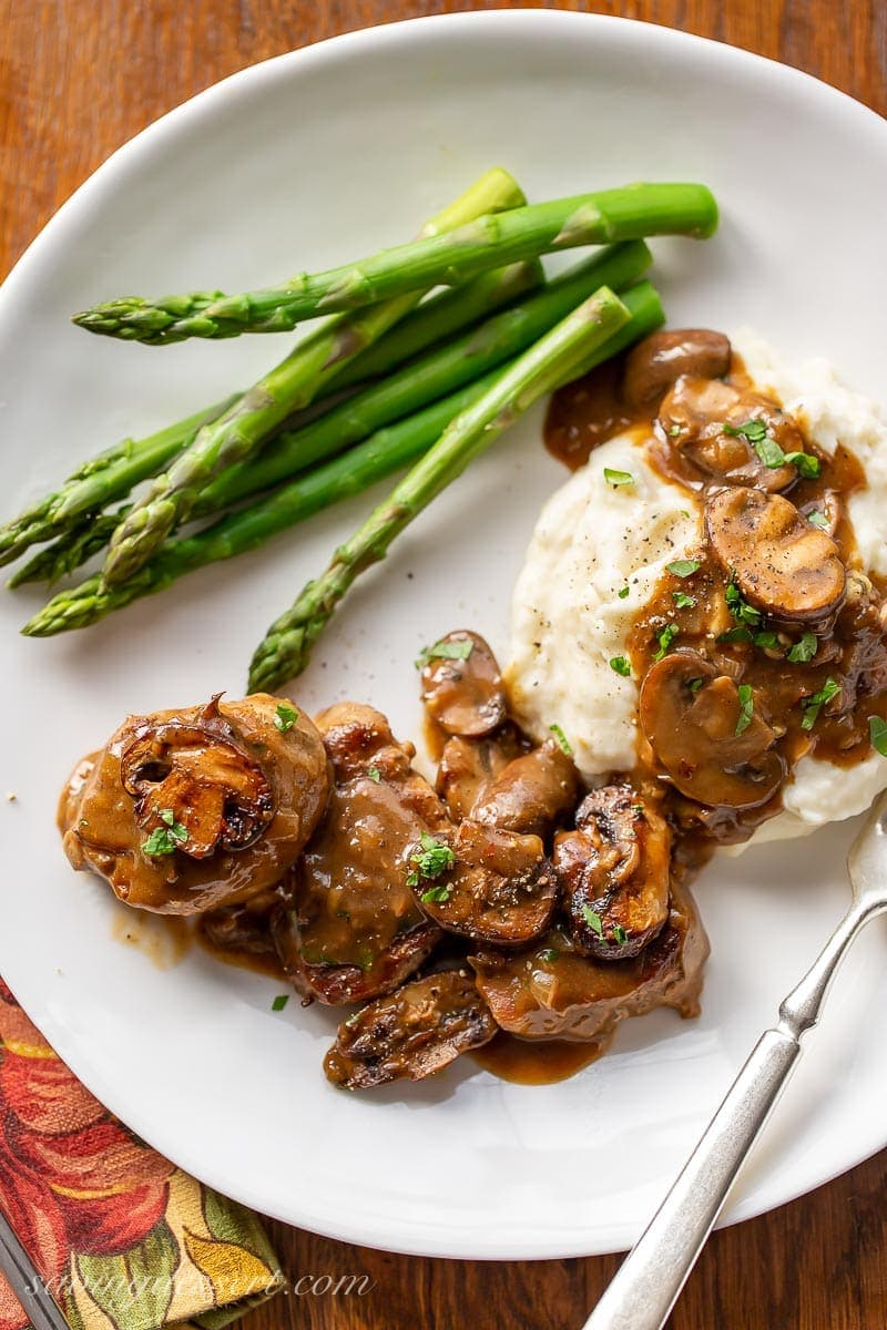 A plate with pork medallions, mushroom gravy, mashed potatoes and asparagus