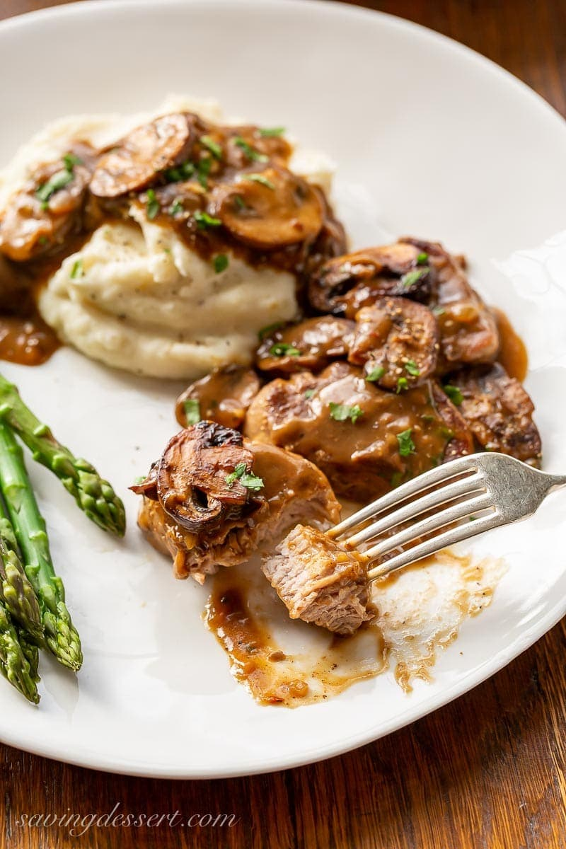 Fork tender pork medallions with mushroom gravy served over mashed potatoes with asparagus