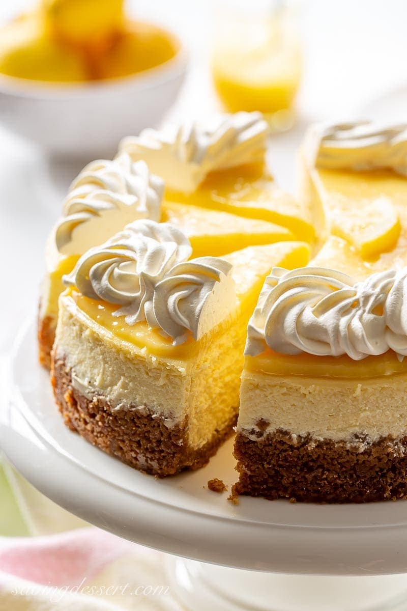 A sliced lemon cheesecake topped with whipped cream on a cake stand