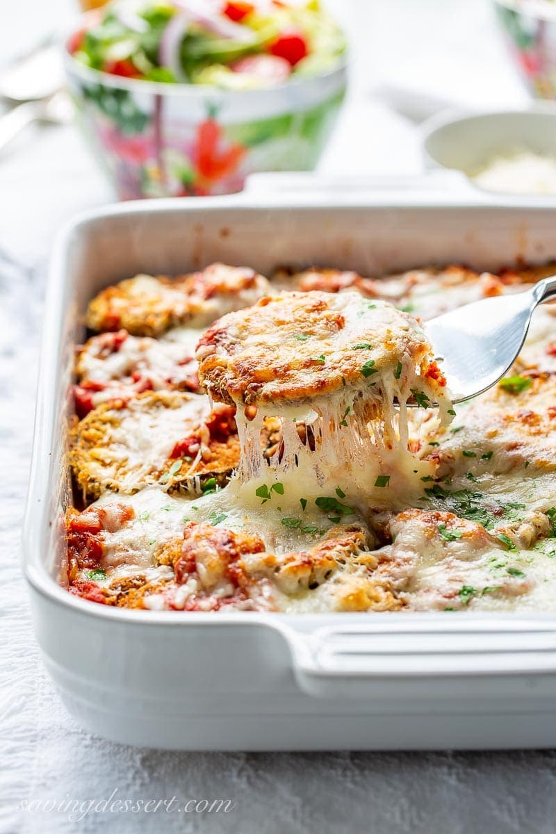 A casserole dish with a scoop of eggplant parmesan on a fork with dripping, gooey cheese