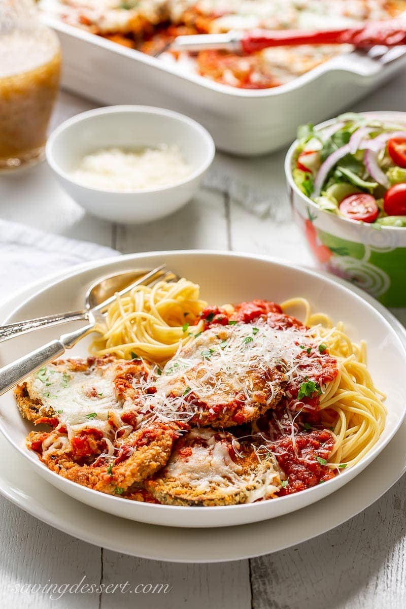 A bowl of spaghetti topped with eggplant Parmesan and served with a side salad and extra grated Parmesan in a bowl