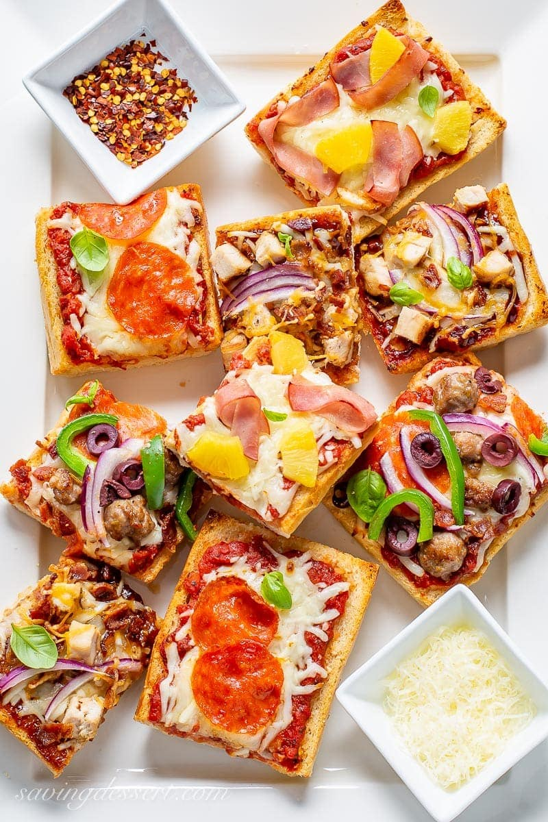 A platter of sliced French bread pizzas with a variety of topping served with red pepper flakes and fresh grated Parmesan