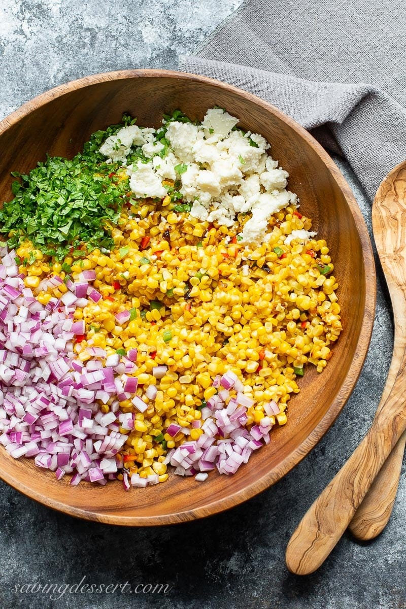 A wooden bowl with fresh corn, red onion, Queso Fresco cheese and chopped cilantro