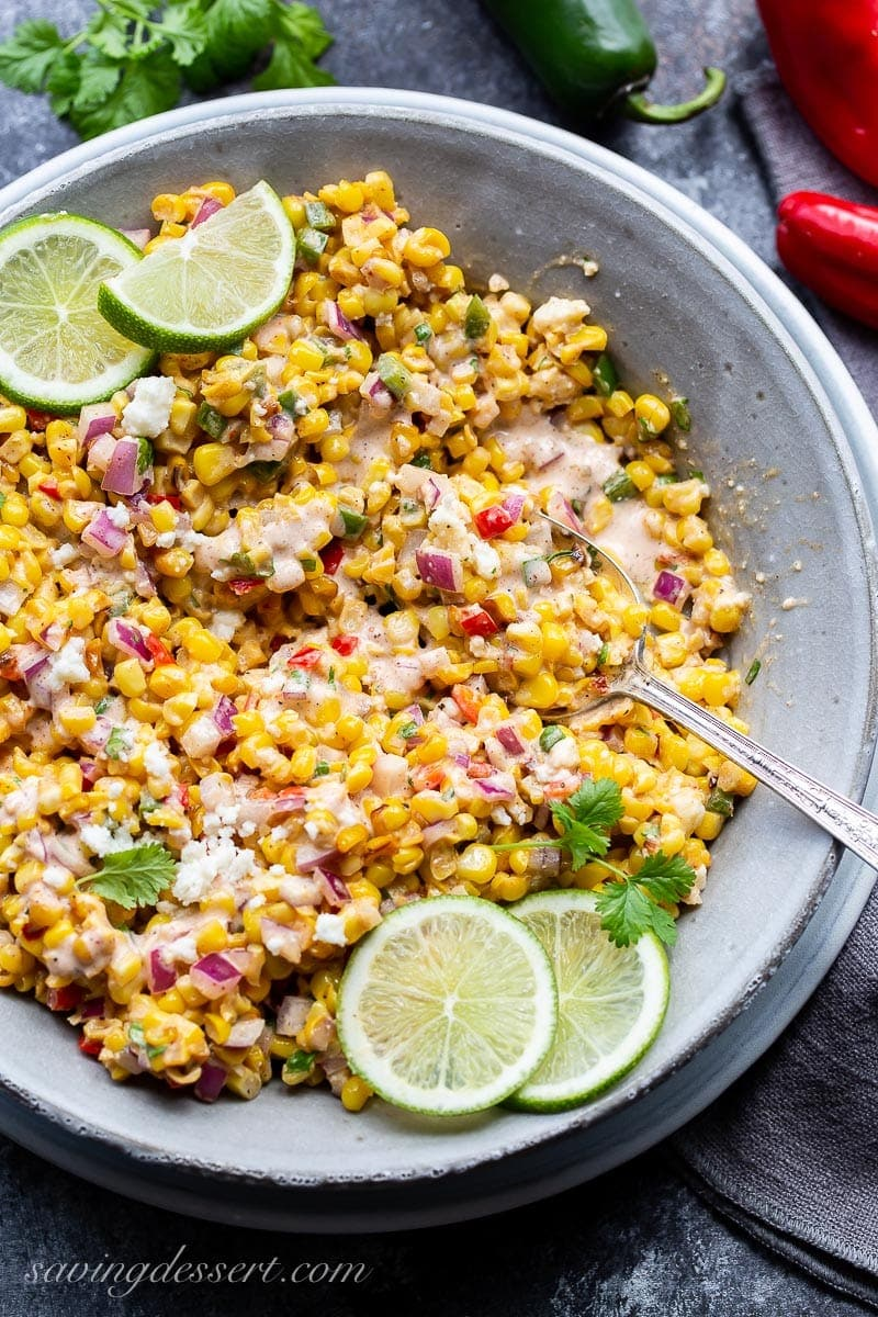 A bowl of Mexican Street Corn Salad garnished with fresh lime wedges and chopped cilantro