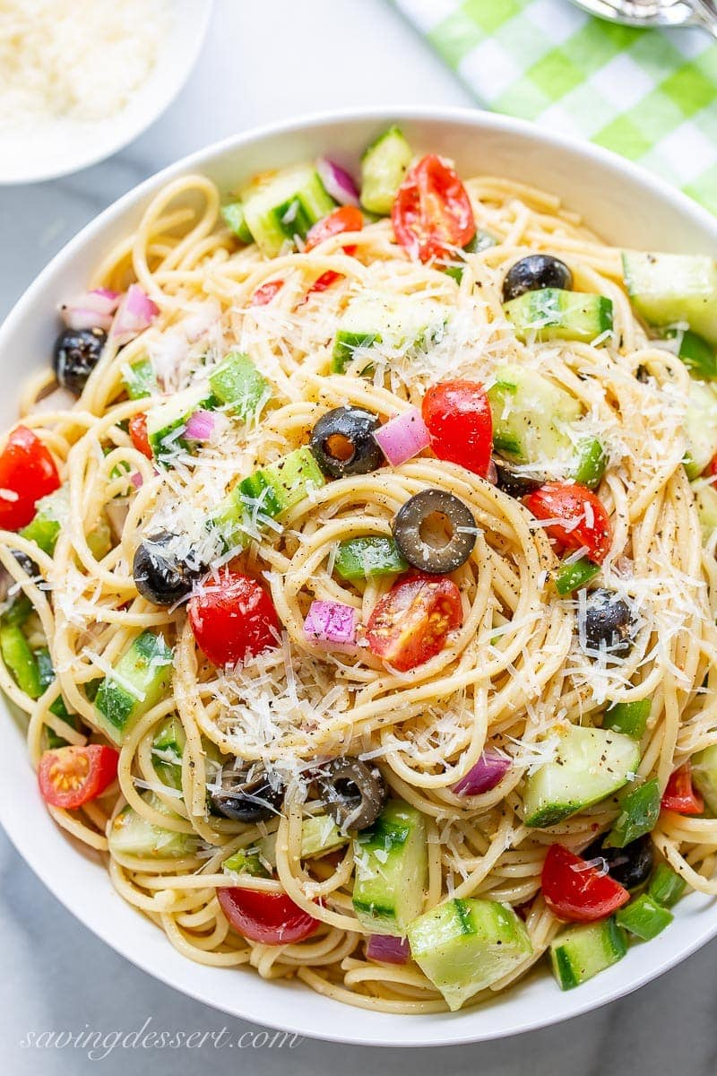 An overhead view of a bowl of cold spaghetti salad with Parmesan and vegetables