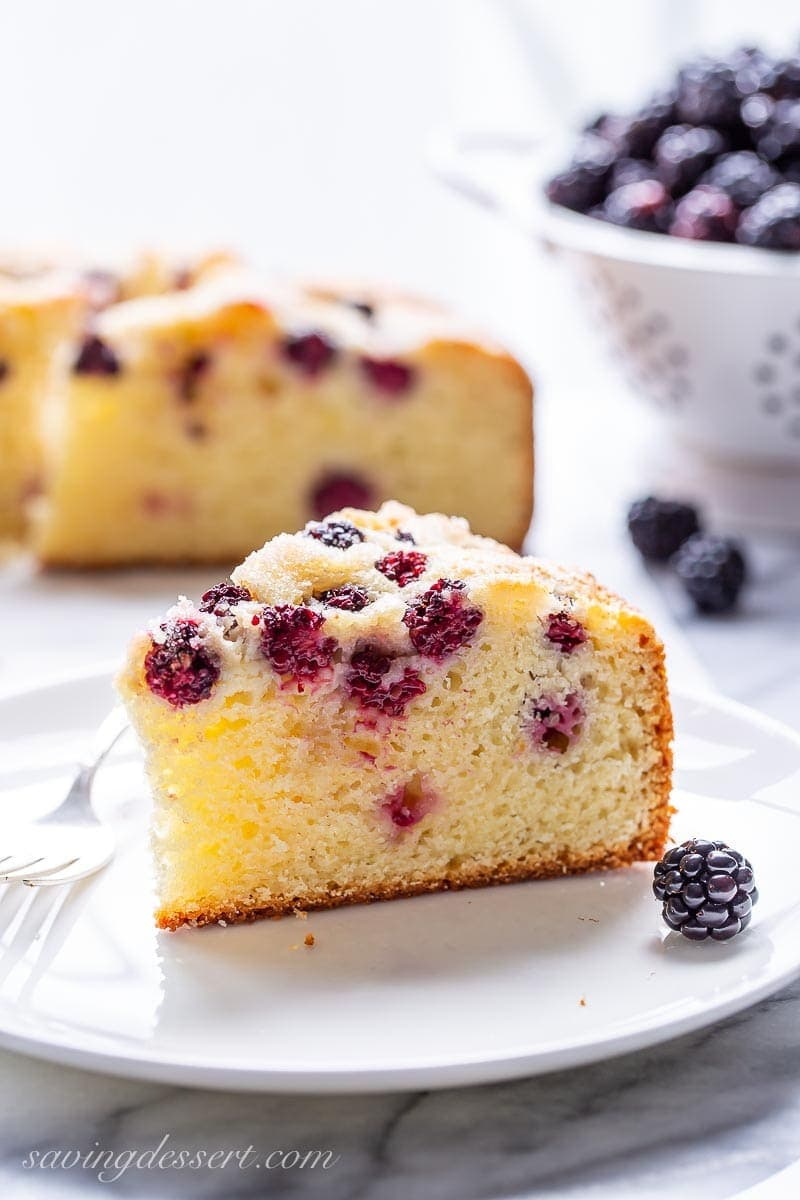 A slice of blackberry breakfast cake on a plate with fresh blackberries