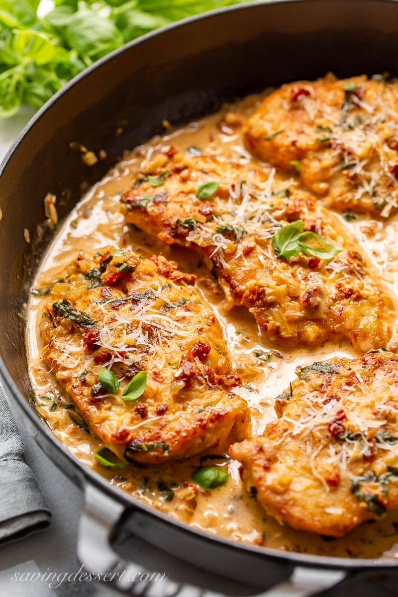 A skillet with sun-dried tomato cream sauce over chicken cutlets