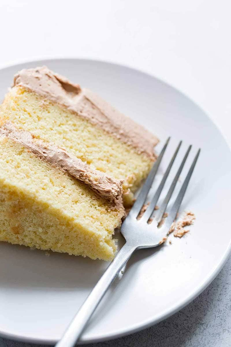 A slice of yellow cake with chocolate buttercream