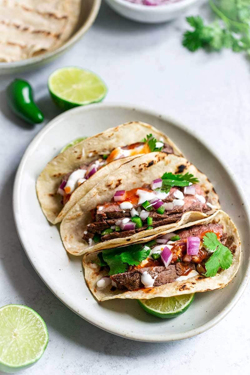 Three grilled flank steak tacos on an oval plate, surrounded by recipe ingredients.