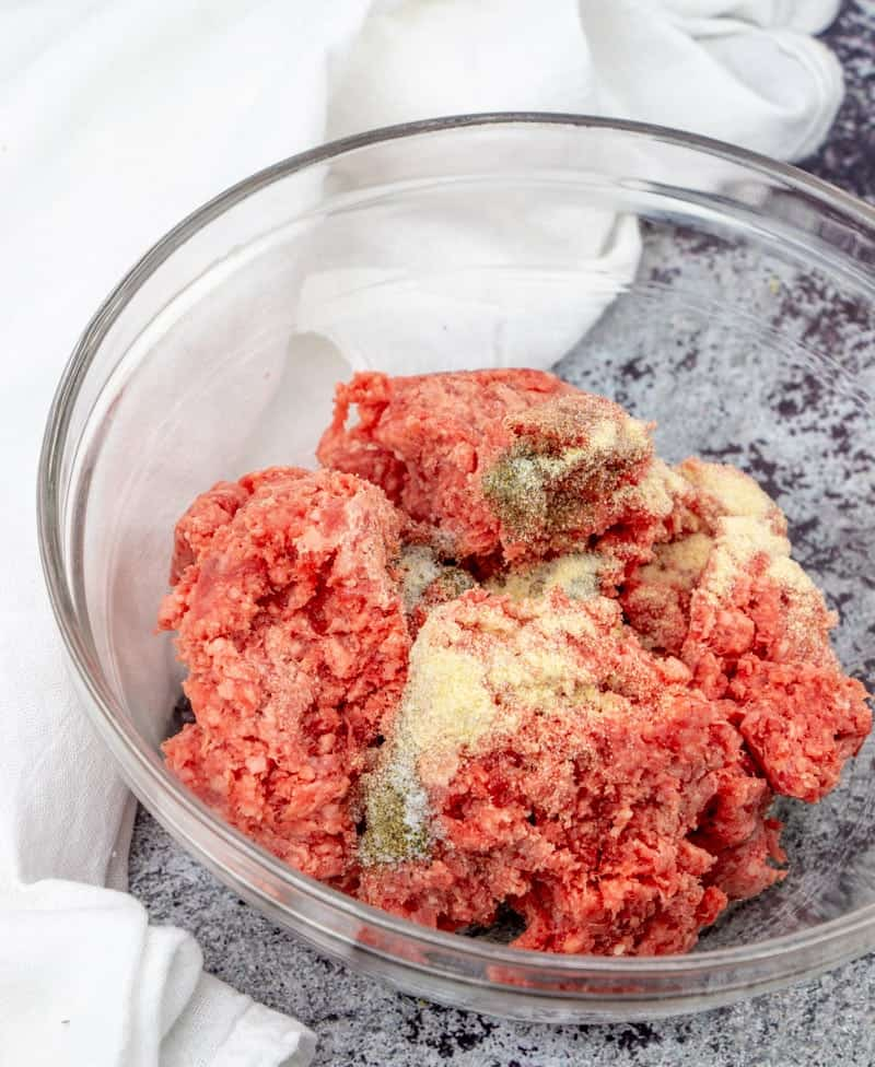 ground beef, onion powder, garlic powder, salt and pepper mixed together in a bowl