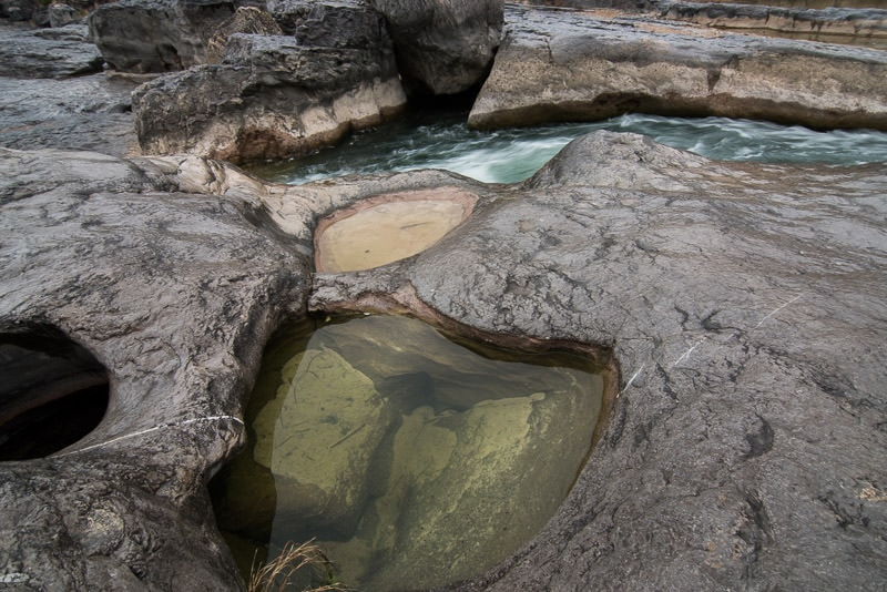 Water flowing through a crack in the rocks with a pool of water in a small pocket in the limestone