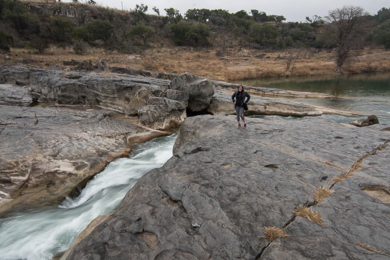 Brooke posing next to the flowing water of the Pedernales River