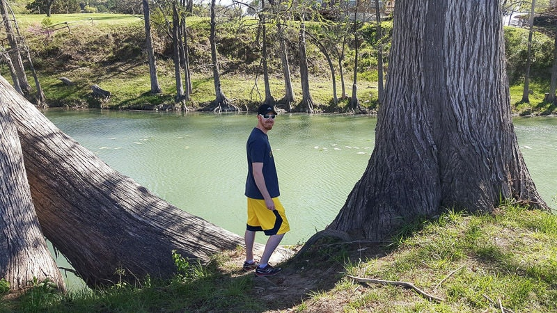 Buddy standing between two large trees as he looks into the river for fish and turtles