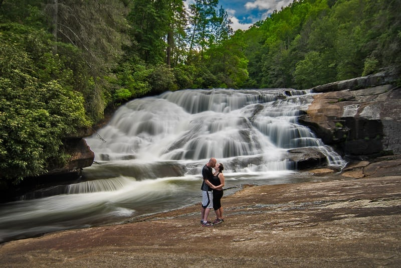 Brooke and Buddy kissing at the base of triple falls in Dupont State Forest north carolina trying to recreate a photo from their first trip