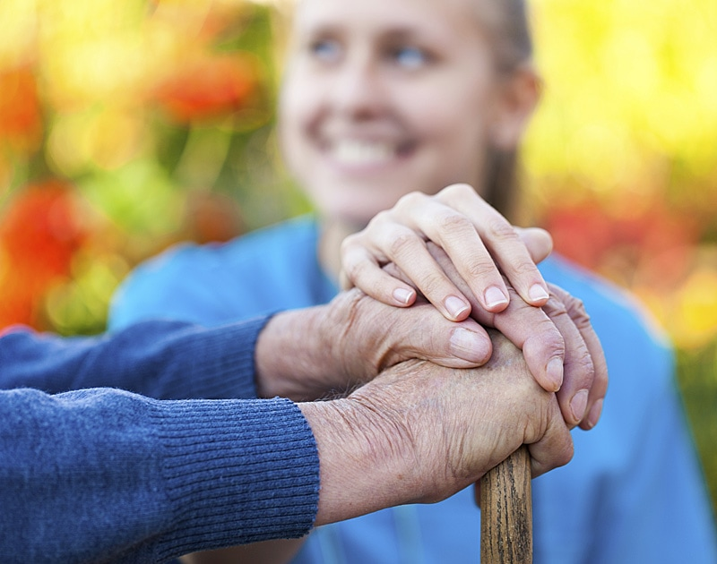 Caregiver with her hadns on top of elderly man's hands