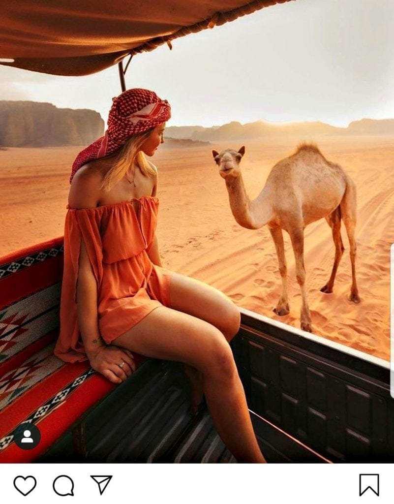 Screenshot of Instagram post with Caucasian woman dressed in traditional Jordanian headdress in skimpy Western dress revealing her shoulders and thighs. A camel looks on.