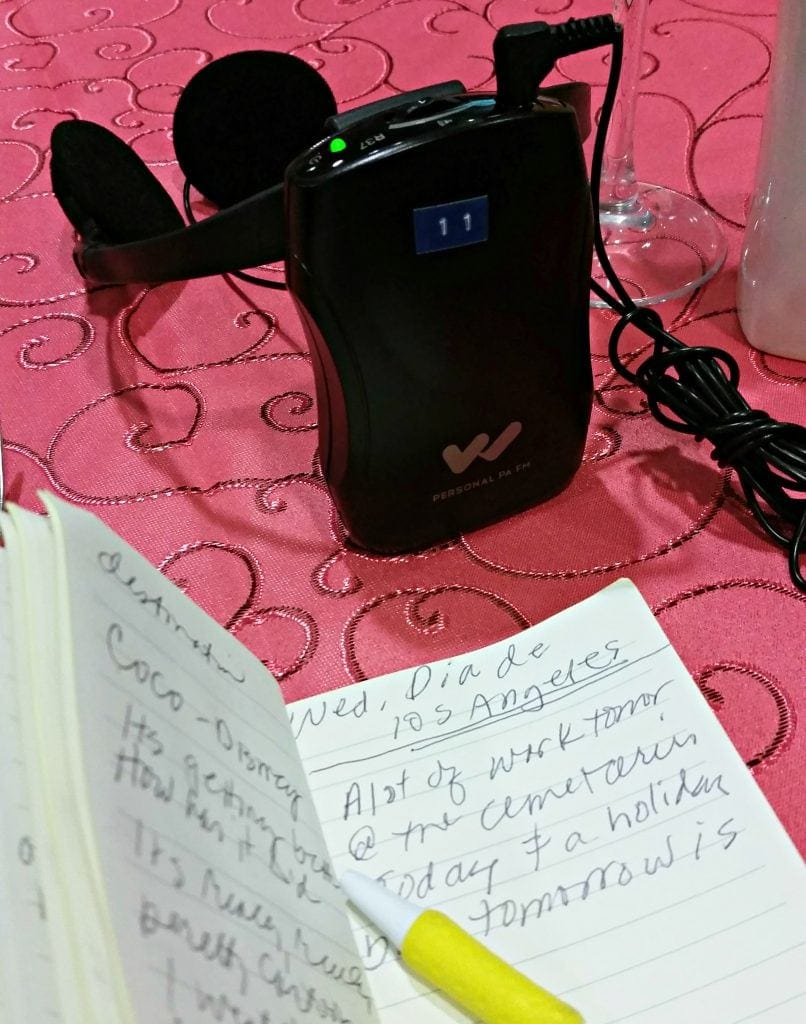 Headphones and translation device sit on table next to journalist's notes