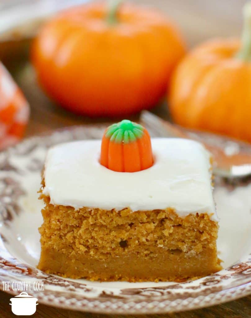 slice of pumpkin pie cake on a brown Spode dessert plate topped with a candy pumpkin