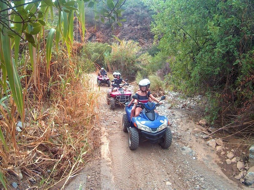 happy quad riders driving over rough terrain amongst greens