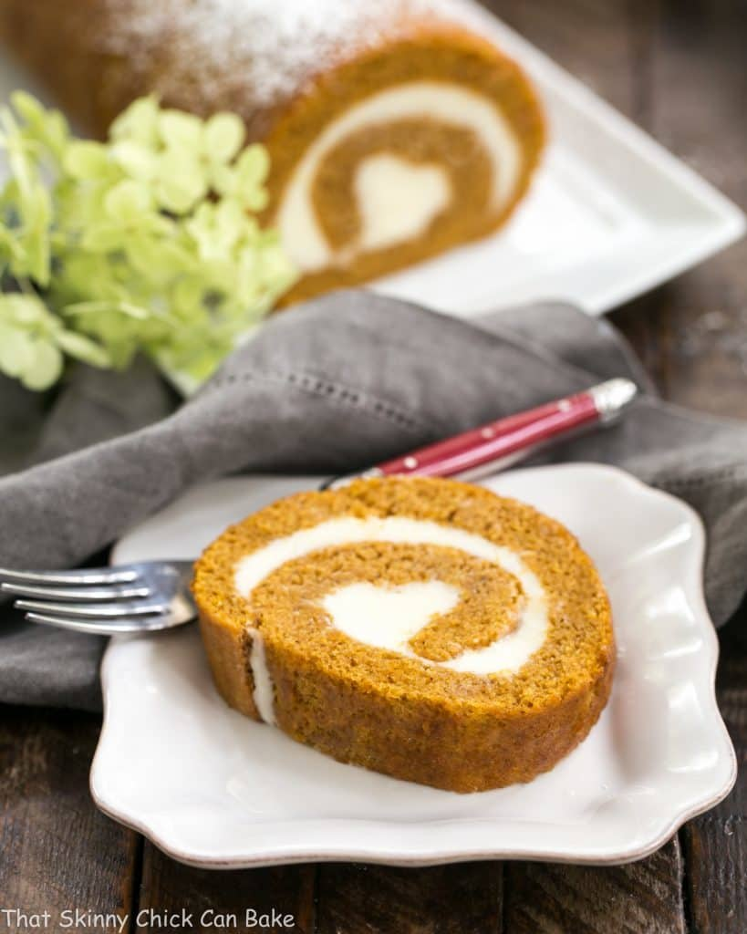 Old Fashioned Pumpkin Roll slice reveals a swirl of cream cheese filling on a white ceramic plate