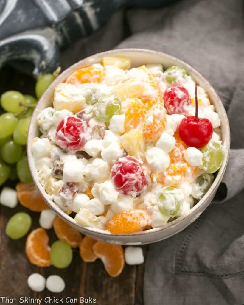 The Best Ambrosia Salad {No Cool Whip} in a white ceramic bowl surrounded by grapes, marshmallows and orange segments