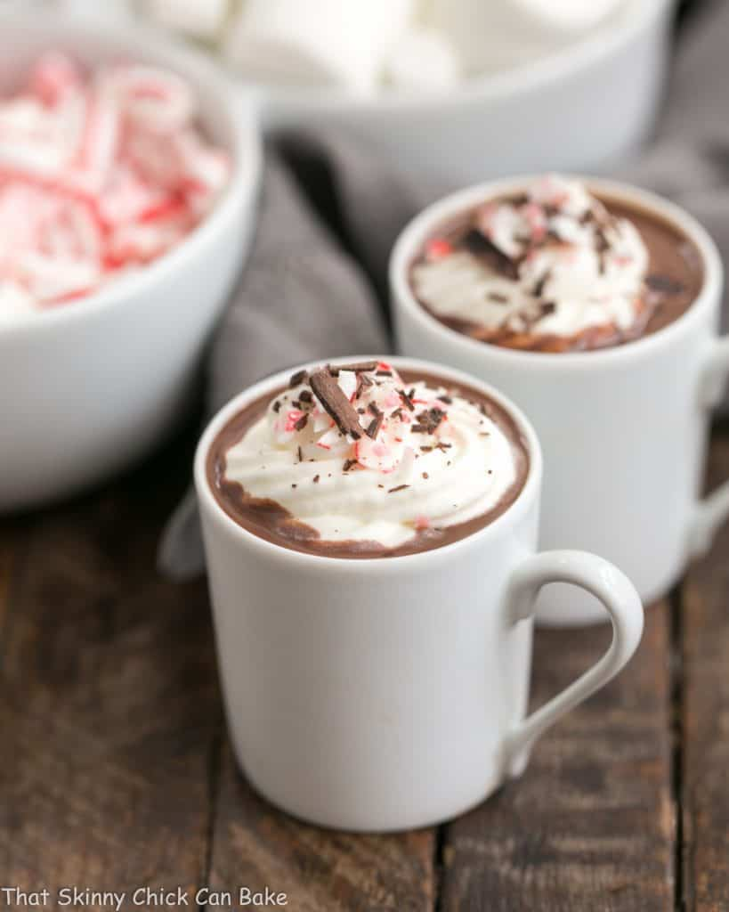 Two mugs of Easy Peppermint Hot Chocolate topped with whipped cream