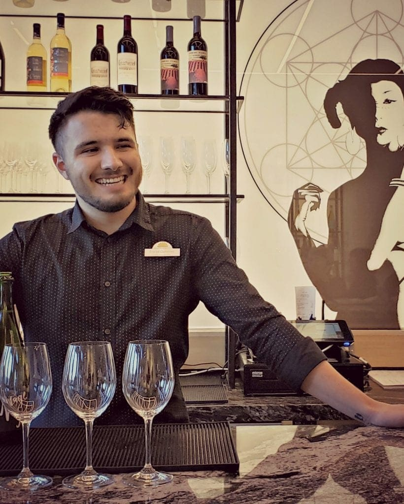 Bartender with big smile stands behind bar with graphic image of woman on wall that seems to be looking over his shoulder. 3 wine glasses are on bar fortastings - one of the things to do in Albuquerque, New Mexico