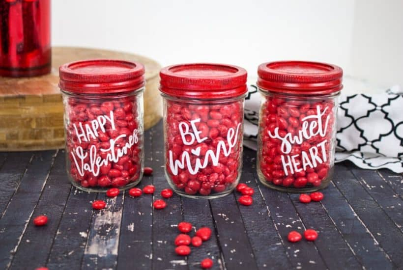 Share some sweetness this Valentine's Day. These Cricut Valentine Candy Mason Jars are a great gift idea for teachers, family and friends. This is an easy Valentine Craft idea to make with your Cricut Machine. This Cricut craft project is a perfect way to celebrate Valentine's Day. #cricutcraft #masonjars #valentinesday #valentinecraft